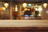 wooden table in front of abstract restaurant lights background - 143551164