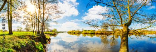 Panorama einer Landschaft im Frühling am Fluss mit Sonne, Wiesen und Bäumen