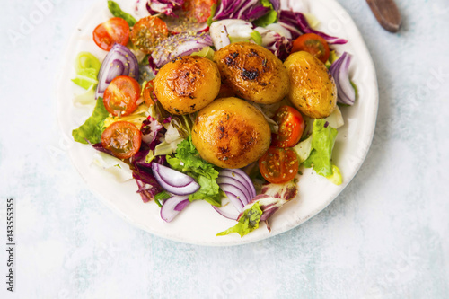 Spiced roasted potatoes with fresh organic vegetables salad with tomatoes, lettuce, onion - 143555355
