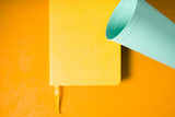 Blue plastic cup with notebook on the yellow background top view
