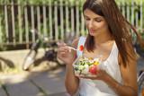junge frau ist in der stadt unterwegs und isst einen salat - 143581736