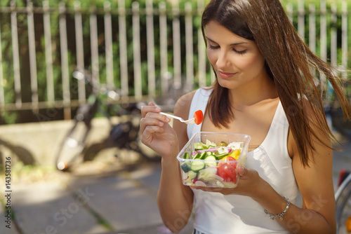Foto Murales junge frau ist in der stadt unterwegs und isst einen salat