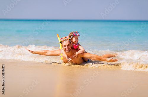Fotografiet Happy family father and child wearing mask and laughing  on beach