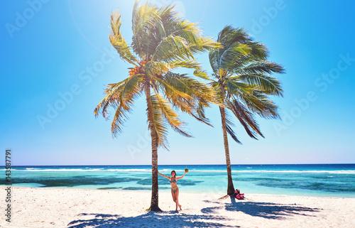 Young woman on beach cheerful joyful  coconut  palm trees. Beach  Caribbean Sea, Cuba