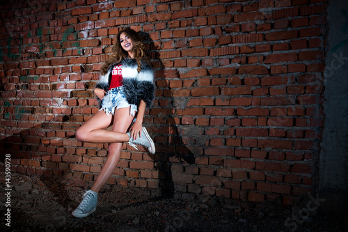 Plakat Stylish cool cool girl in short shorts with a red T-shirt and fur coat, with cur