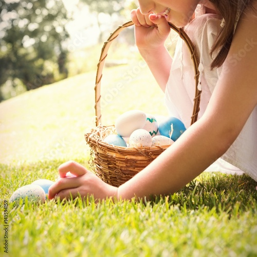Little girl collecting easter eggs - 143594159