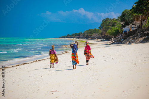 Staande foto Zanzibar Three women walking on the beach in Jambiani, Zanzibar island, Tanzania