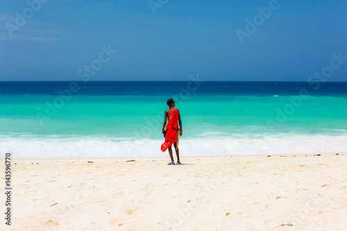 Poster Zanzibar masai on a beach and blue sea on the background