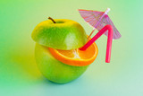 Fruit cocktail on a colorful background with a straw and an umbrella. Apple and orange