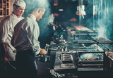Fototapety Food concept. Chef in white uniform monitors the degree of roasting and greases meat with oil in saucepan in interior of modern restaurant kitchen. Preparing traditional beef steak on barbecue oven.