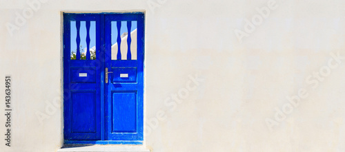 Foto op Canvas Santorini Blue door on a whitewashed wall - Cyclades, Greece