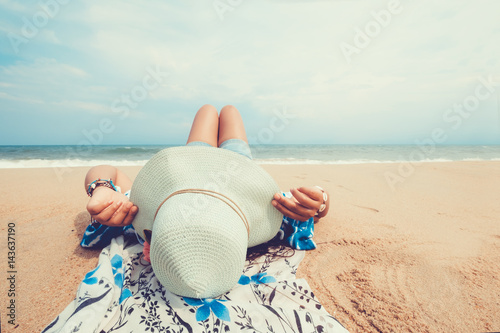 Leisure in summer - Young women lying on a tropical beach, relax with hat. Blue sea in the background. Summer vacation concept. vintage color tone.