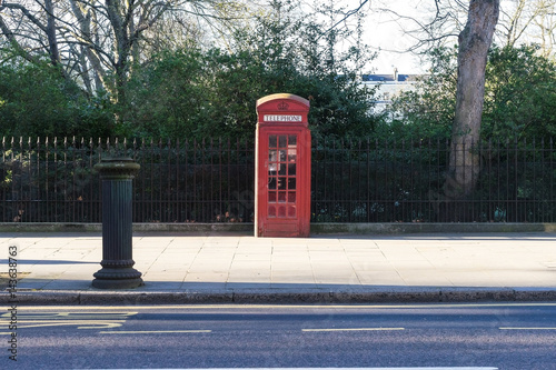 London - March 30: Iconic telephone booth in Kensington Garden in front of park with fence on March 30, 2017 Poster