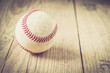 Old baseball ball on wooden background and highly closeup