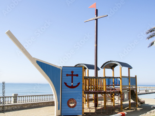 Playground shaped like a wooden boat by the sea