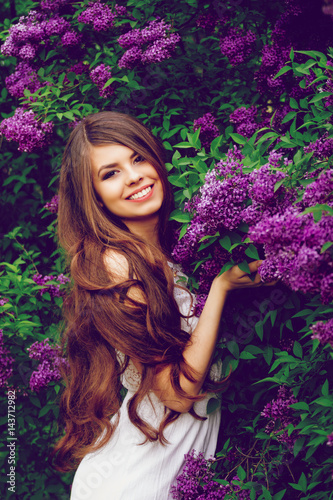 young beautiful girl in spring in a white dress , in the Botanical garden with blooming lilacs ,
