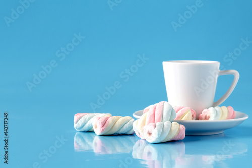 cup of coffee with american twisted marshmallow on blue background with copy space