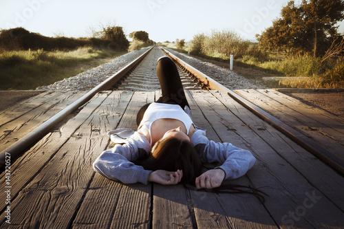 Joven tumbada en las vías del tren mirando a la derecha.