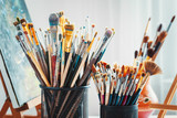Fototapety Artistic equipment in studio: wooden easel,  paintbrushes, tubes of paint, palette and paintings on work artist table.
