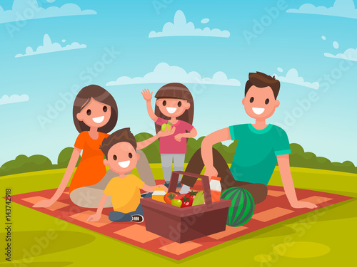 Happy family on a picnic. Dad, mom, son and daughter are resting in nature