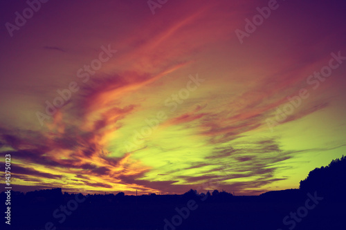 Rural landscape after sunset. Silhouette of village against colorful sunset sky