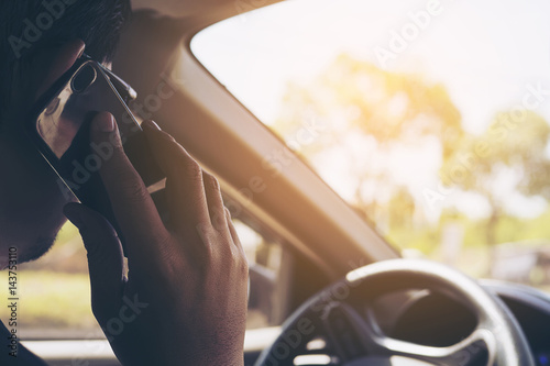 Poster Close up of a man driving car dangerously while using mobile phone