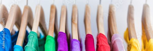 Banner crop for copyspace texture for text of clothing rack. Clothes hanging on hangers in home closet or shopping mall for store sale concept. Colorful outfits collection. Panorama ad.