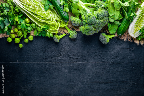 Collection of fresh green vegetables placed on black stone