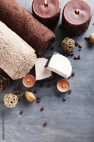 Towels with candles and soap on grey wooden table