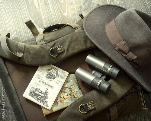Hat, Binoculars, passport, backpack, notepad lie together for travel on wood floor