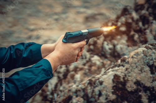 man with pistol shooting. hitman in ambush firing the gun. Poster