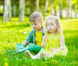 Little girl and boy sitting together on green grass with dandelions