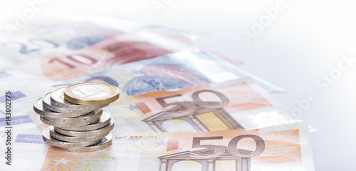 Leinwanddruck Bild Euromünzen im Stapel auf  Eurogeldscheinen, Panorama, Hintergrund