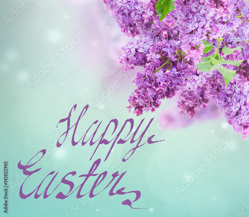 Bush of of purple Lilac flowers on blue sky bokeh background with happy easter greetings