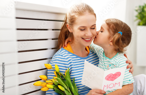 Happy mother's day! Child daughter congratulates moms and gives her a postcard and flowers