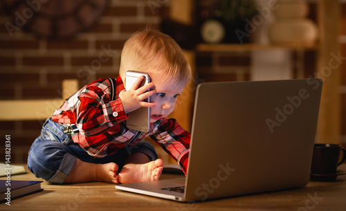 concept of baby boy working on computer and talking on phone