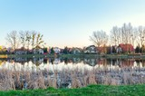 Spring urban landscape. Houses on the pond on the outskirts of town.