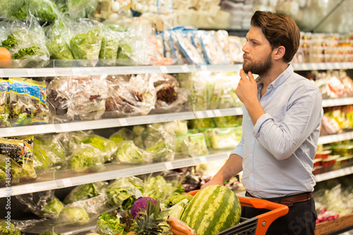 Keuken foto achterwand Boodschappen Young bearded man doing groceries at the local store