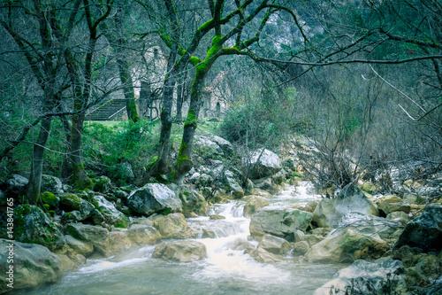 Río bajo caserón abandonado