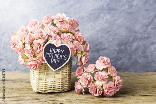 Happy mothers day concept of Paper carnation in weave basket on old wood with co Poster