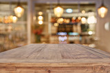 wooden table in front of abstract restaurant lights background - 143876149