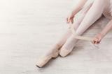 Fototapety Ballerina puts on pointe ballet shoes, graceful legs