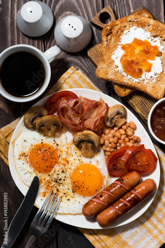 Fried eggs with bacon, sausages and vegetables for breakfast, vertical top view