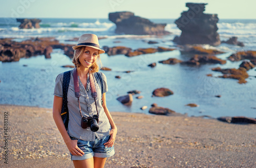 Travel and hobby. Pretty young woman with camera and rucksack on the ocean beach.