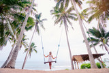 Vacation concept. Happy young woman in white dress and hat swinging at palm grove enjoying sea view.