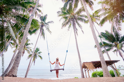In de dag Bali Vacation concept. Happy young woman in white dress and hat swinging at palm grove enjoying sea view.
