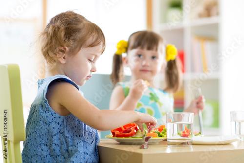 Fotografiet kids children eating vegetables in kindergarten or at home