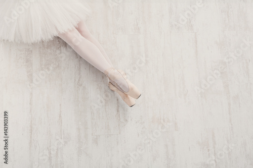 Ballerina in pointe ballet shoes, graceful legs with copy space