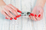 Woman hands with bright trendy red manicure holding pliers and squeezing one nail