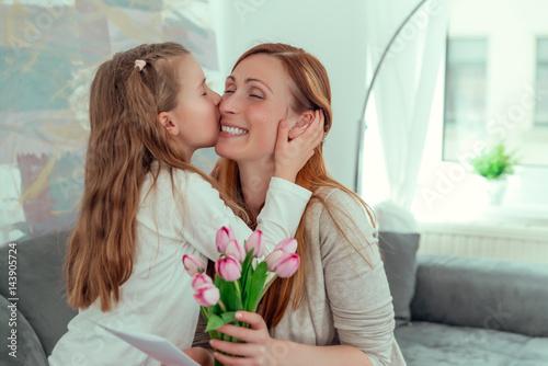 Fotografiet kind gratuliert mama zum muttertag mit blumen